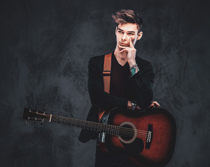 Young attractive man is playing acoustic guitar at studio while posing for photographer.