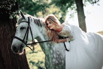Beautiful and stunning bride, riding a horse in the nature