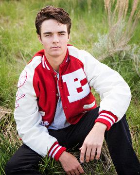 High school senior male posing in his letter jacket.