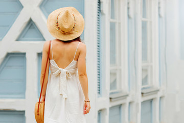 Wall Mural - Young woman in light summer clothes and straw hat  with bamboo handbag. Summer Vacation concept