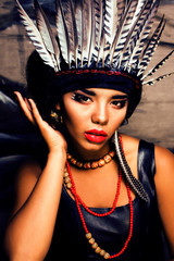 young pretty woman with make up like red indian, futher in hair, fashion hallowen concept