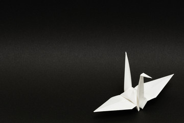 white origami paper crane on black background