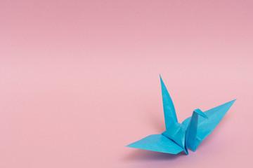 light blue origami crane on pink background