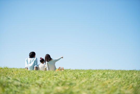 草原でピクニックをするファミリーの後ろ姿