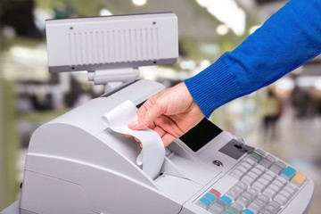 Fototapete - Cash register with LCD display and worker's hand holding receipt paper over blurred supermarket interor
