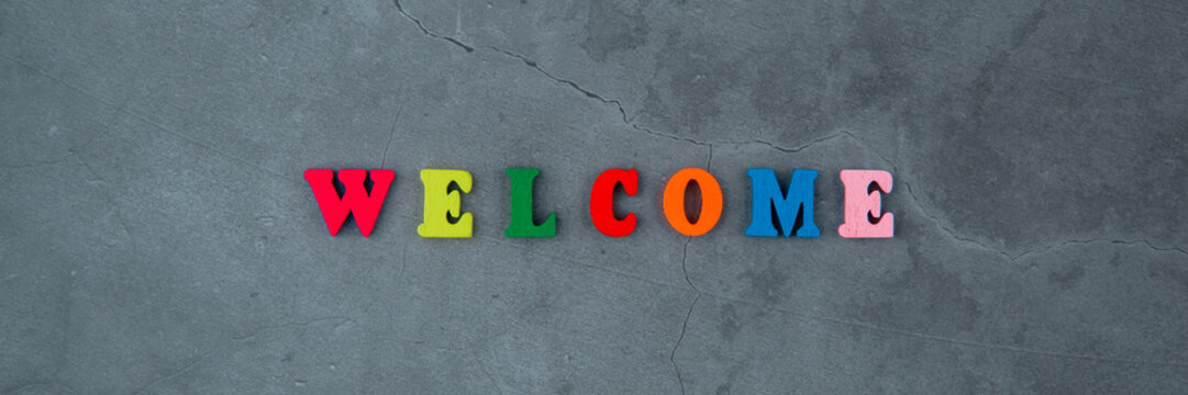 The multicolored welcome word is made of wooden letters on a grey plastered wall background.