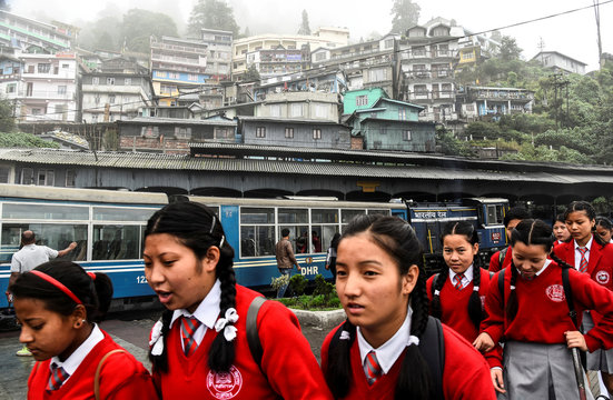 School children walk past a parked Darjeeling Himalayan Railway train, which runs on a 2 foot gauge railway and is a UNESCO World Heritage Site, at a station in Darjeeling