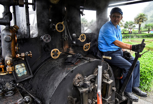 Train driver Hari Chettri sits in the engine of Darjeeling Himalayan Railway steam train, which runs on a 2 foot gauge railway and is a UNESCO World Heritage Site, as it leaves Batasia Loop in Darjeeling