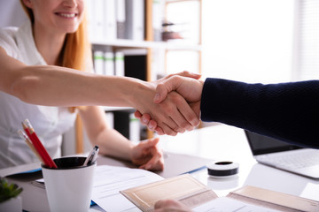 Businesswoman Shaking Hand With Her Colleague Over Desk