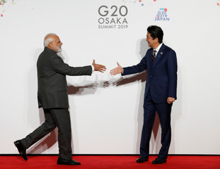 India's Prime Minister Narendra Modi is welcomed by Japanese Prime Minister Shinzo Abe upon his arrival for a welcome and family photo session at G20 leaders summit in Osaka