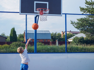 Little boy playing basketball outdoors at summer day