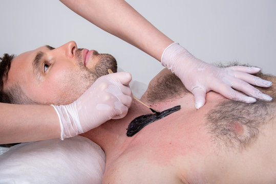 Closeup of male chest with hair and wax. Professional shugaring master in gloves makes depilation to a young man in the salon