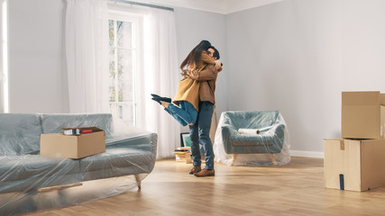 Happy and Excited Young Couple Look Around In Wonder at their Newly Purchased / Rented Apartment. Girl Jumps Into His Boyfriend's Arms Hug. Big Bright Modern Home with Cardboard Boxes Ready to Unpack.
