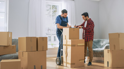 Happy New Homeowner Welcomes Professional Mover with Hand Truck full of Cardboard Boxes, Receives His Goods and Signs on Clipboard. Wall mural