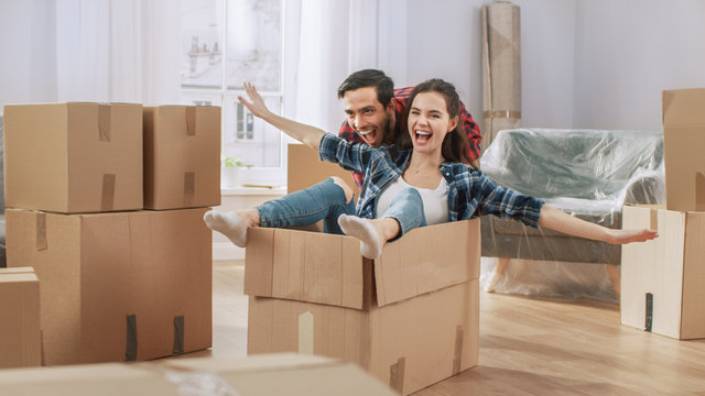 Young Couple Moving Into New Apartment, Boyfriend Drives Girlfriend in Cardboard Box, She imitates Airplane Wings. Young Boyfriend and Girlfriend Start Living Together, Unpacking Stuff, Having Fun.