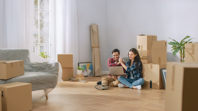 Happy Young Couple Sitting on Floor of Newly Rented / Purchased Apartment Use Laptop Computer. Successful Boyfriend and Girlfriend do High Five. Cardboard Boxes and Covered Furniture in Bright Home