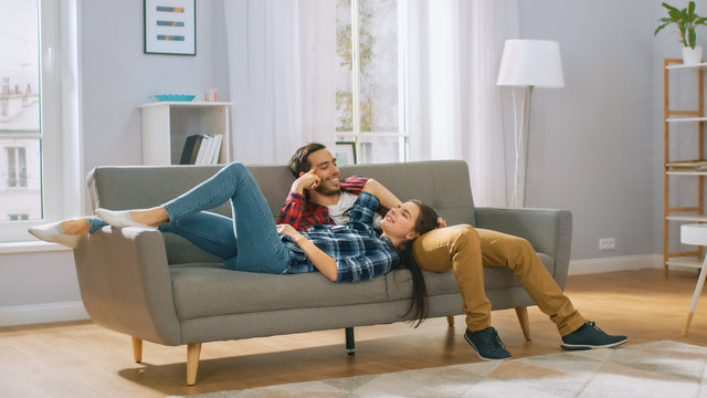 Happy Young Couple is Lying on a New Couch in the Living Room and Having a Rest. Bright Modern Apartment with Stylish Furniture.