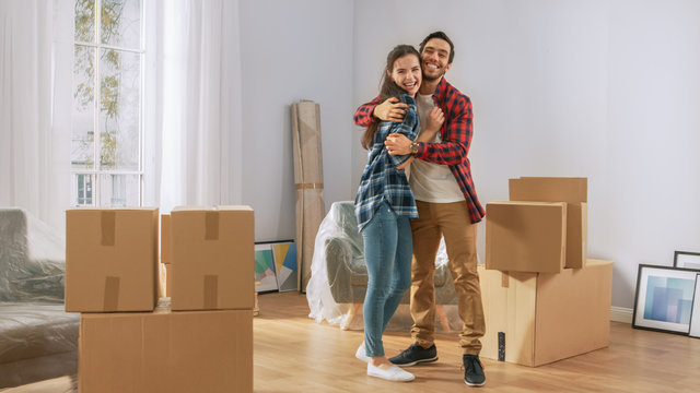 Happy Young Couple Moving Into New Apartment, Carrying Cardboard Boxes with Stuff, Having Fun and Hugging. Young Boyfriend and Girlfriend Start Living Together, Unpacking Stuff.