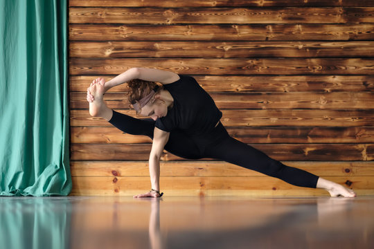 Advanced yoga asana. Curly woman working out, doing side plank pose with stretching.