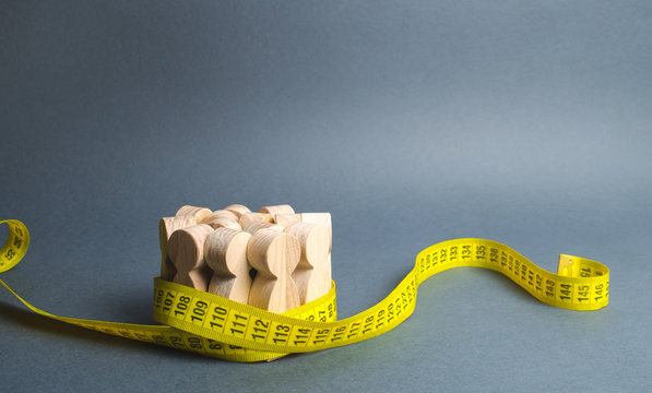 A crowd of wooden figures Gripped by measuring tape. Social Sciences. Promotion of ideas for weight loss, lifestyle. Information statistics, measurement of the number, trends of population growth.