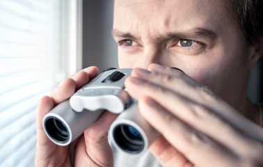 Man with binoculars. Private detective, agent or investigator looking out the window. Man spying or investigating. Privacy, surveillance or espionage concept. Suspicious or curious person spying. - fototapety na wymiar
