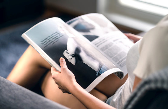 Happy millennial lady reading fashion magazine with latest beauty trends or celebrity news and interview articles. Woman sitting on couch with open page. Young person relaxing and enjoying fun leisure