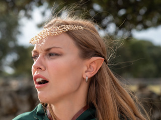Close-up of blonde girl with blue eyes and elf ears wearing a green cape