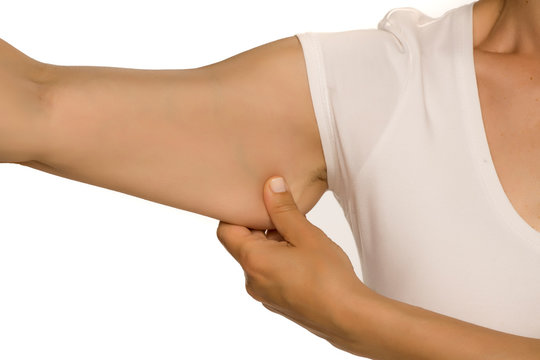 Woman pinching a fat on her arm on white background