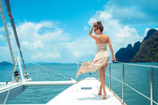 Outdoor shot of adorable young woman in a beige dress standing on edge of yacht, looking to beautiful nature landscape during trip. Happy woman enjoying summer travel. Back view