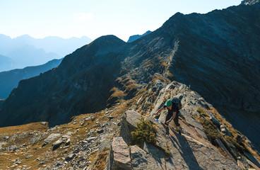Fotomurales - Hiker on a narrow ridge in the mountains. Via Alta Verzasca, Switzerland.