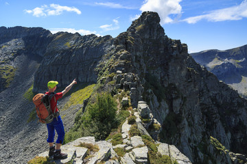 Fotomurales - Hiker pointing at the ridge he just climbed over. Ticino, Switzerland.