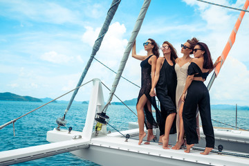Four women in evening dress standing close to each other. They drinking champagne.  Young women smile and enjoy time. Luxury vacation on the yacht