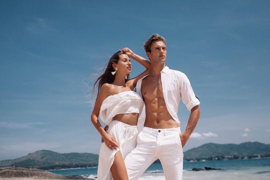 Fashion photo of a beautiful  fitness happy couple in white clothes in love standing  and posing on the beach. Phuket. Thailand