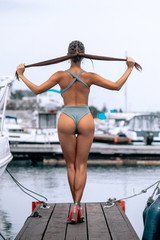 Back view of Sexy shape beautiful Brunette Woman with perfect buttocks standing on the wooden pier. Commercial advertisement for tourism. Blurred yachts background