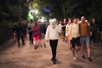 A man with a polar bear mask walks through the South East Corner area of Glastonbury Festival in Somerset