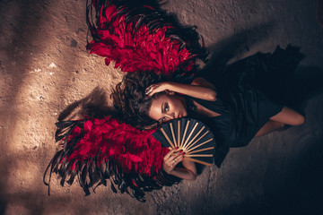 Fashion portrait of a passion woman wearing black dress with red angel wings and with black fan in her hand. Dark beauty fashion concept.