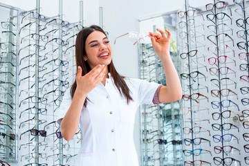 Attractive young female doctor in ophthalmology clinic. Doctor ophthalmologist is standing near...