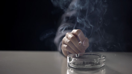 Business woman holding cigarette under ashtray, nicotine dependence, closeup