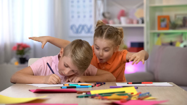 Girl scaring brother studying at table, child hyperactivity, attention deficit