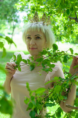 the beautiful Russian woman with a crown on the head walks in the forest in the summer