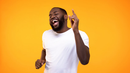 Happy relaxed black man dancing against yellow background, having fun on party Wall mural