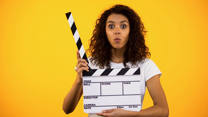 Shocked producer assistant holding clapper board, shooting movie film production
