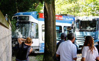 Members of the media take pictures at the site of an accident after a truck crashed into a tram in Zurich