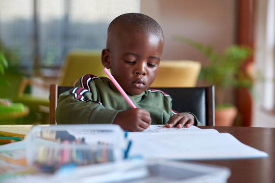 Young artistic boy drawing at home
