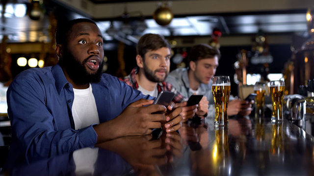 African-american man checking bets on smartphone, watching match in bar, app