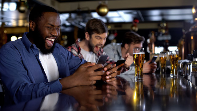 Emotional african-american male celebrating winning bet on match, bookmaker app