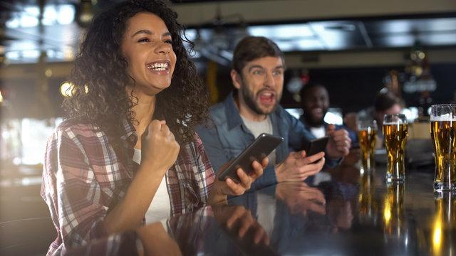 Smiling biracial woman in pub celebrating winning sports bet, bookmaker app