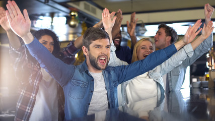 Excited sport fans clapping hands in bar, cheering team, celebrating victory