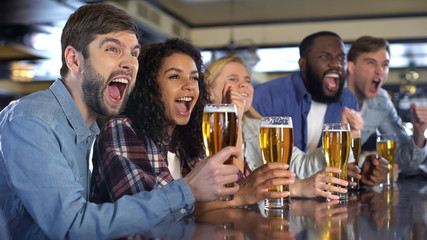 Emotional sport fans with beer glasses celebrating team victory in brewery pub