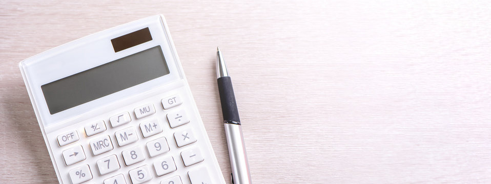 White calculator and pen on bright wooden table, analytics and statistics of financial profit, investment risk concept, copy space, top view flat lay
